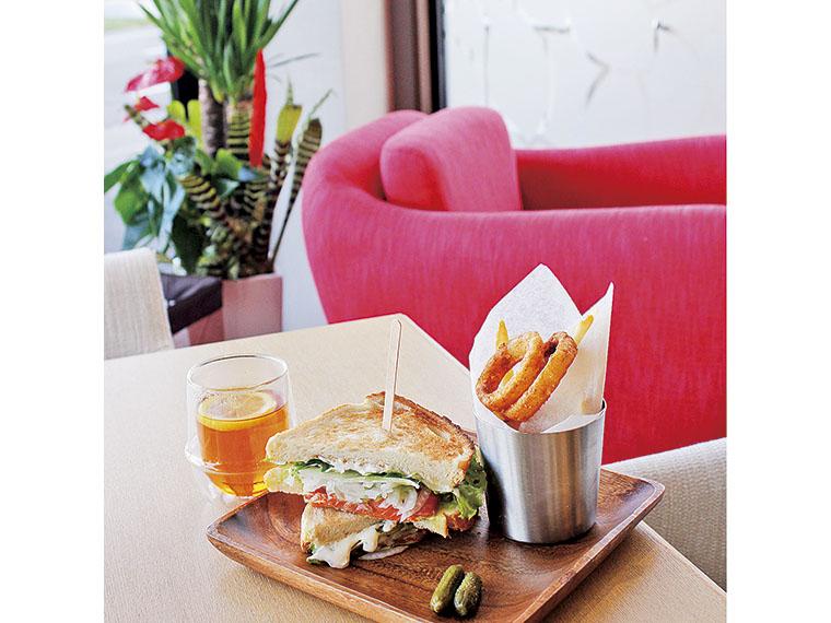 「サーモンアボカドサンドイッチ」(単品1,296円)。トリュフ塩をかけたフレンチフライとオニオンリング付き。「ダージリン」(単品324円)