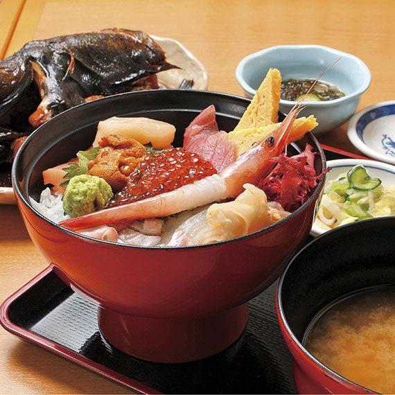 小鉢、みそ汁、お新香が付いた海鮮丼。他ではなかなか味わえないドンコの煮付け(左奥)は、日替わりの「煮魚定食」(時価)で味わえる
