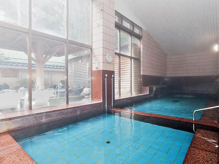 明るく開放的な大浴場。清掃の行き届いた清潔さと、かけ流しが人気の理由。男湯・女湯ともにサウナを完備