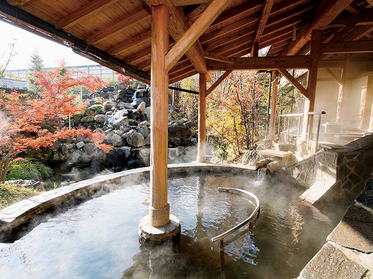 男性露天風呂「もみほぐしの湯」。心地よい小川のせせらぎを聞きながら身体をゆったり温めるひと時。夜は趣が変わり幻想的に