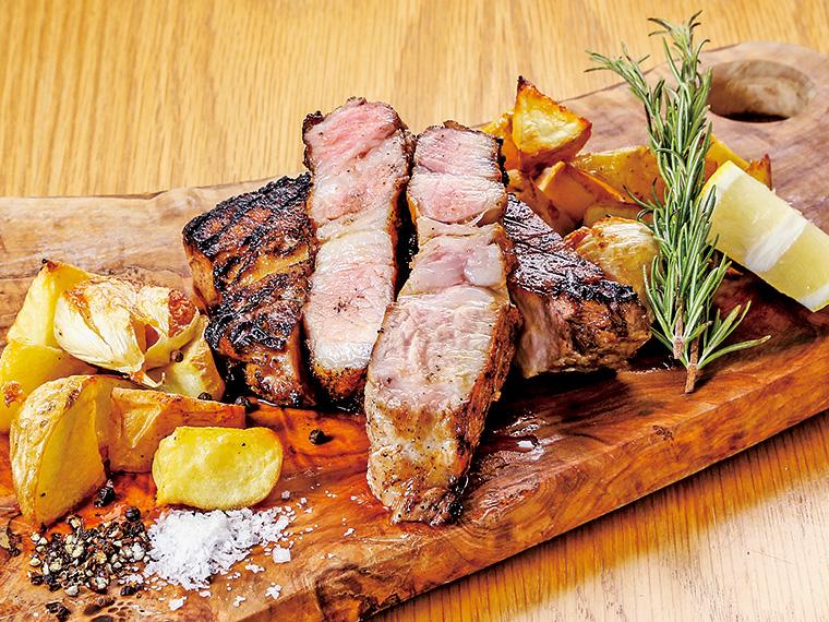 【しらさわ豚のグリル(400g 3,000円〜・要予約)】赤身と脂身が程良く織り交ざるのも、しらさわ豚の特長。肥育期間を一般的な期間より長くし、ゆっくりと育てられることにより、脂身の味わいは深く、甘くなる。冬には、温かな煮込み料理などでも味わえる