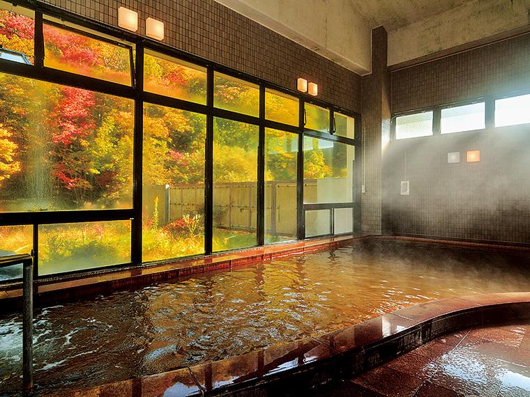 窓の外に紅葉の景色が広がり、開放感あふれる「山桜の湯」の内湯