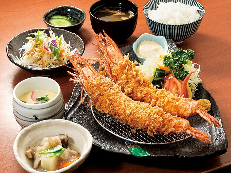 「特大海老フライ定食」(1,900円)。大皿に1尾25㎝ほどの大きな海老フライが2本。小鉢や茶碗蒸し、サラダなども添えられ、まずはそのボリュームに驚かされる。アジフライやカキフライ、煮魚、焼き魚など魚料理の定食は昼夜いずれも人気。なかでも贅沢感たっぷりの特大海老フライは、ぜひ一度は食べてみたい