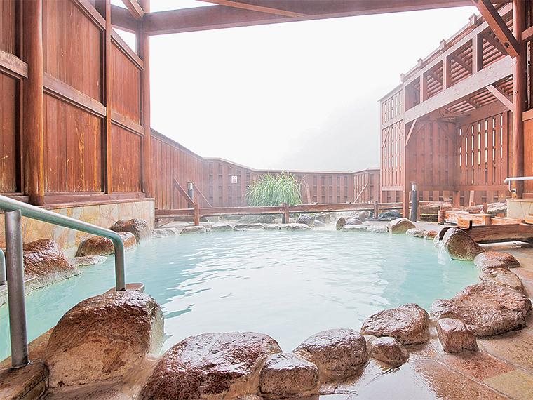 青みがかった乳白色の湯が満ちる岩造りの女性用露天風呂。他に木造りの男性用露天風呂もあります