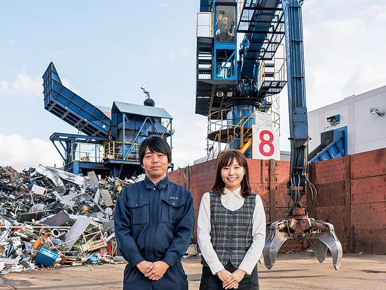 廃棄物を破砕機へと運ぶ巨大なタワークレーンの前に立つ橋本雅人さんと八木沼楓さん