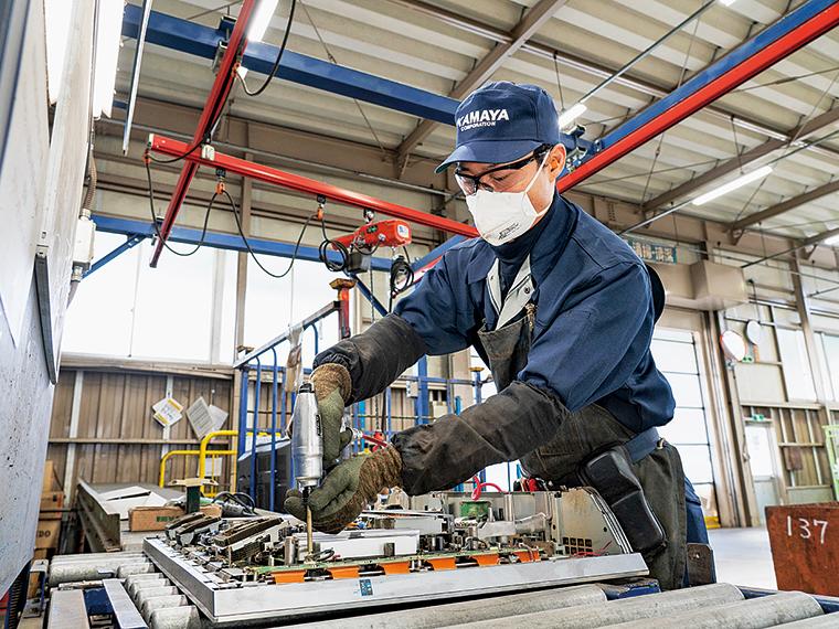 家電の解体を担当する柳田裕偉さん。多いときは1日に100台もこなすという