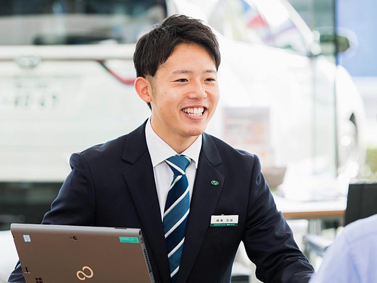 営業の峰島和哉さん。コミュニケーションのツボを学び、笑顔での接客も板についてきた