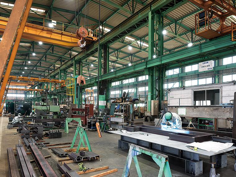大型の機械が目立つ作業現場。図面に基づいて鉄鋼の断裁や溶接などを行う現場風景。やり直しのきかない作業のため真剣な表情が印象的だ