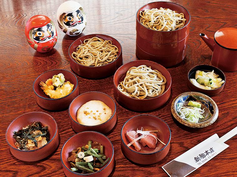 割子そば(1,280円)赤い漆器が重ねられた、白河そばの伝統的な一品。薬味はマグロ、とろろ、山菜なめこ、天ぷら、カツオ節と海苔で、一皿ごとに薬味をのせ、それぞれ違った味が楽しめる
