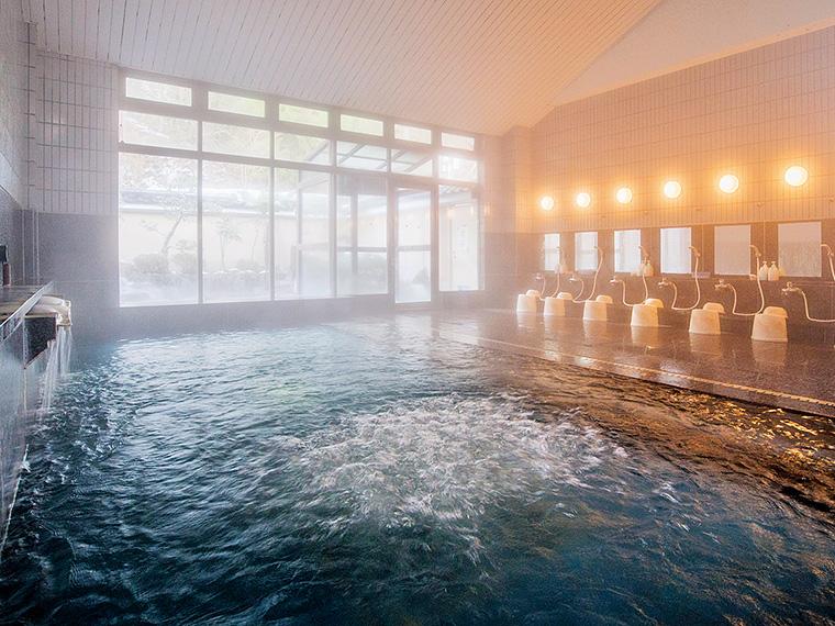 明るく開放的な大浴場。清掃の行き届いた清潔感と、源泉かけ流しが人気の理由。男湯・女湯ともにサウナを完備