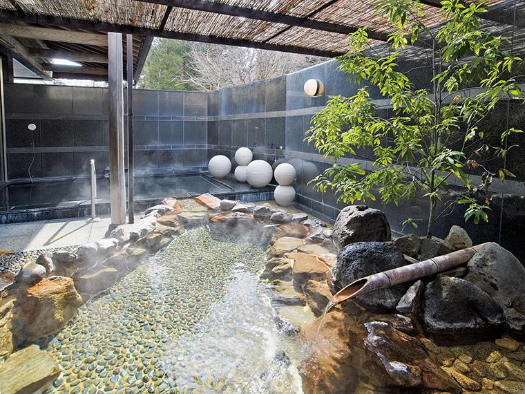 """美肌効果に期待大!肌なじみのよい""""美人の湯""""として知られる磐梯熱海温泉。写真の露天風呂は、岩造りと黒大理石(奥)の湯船が2種類"""