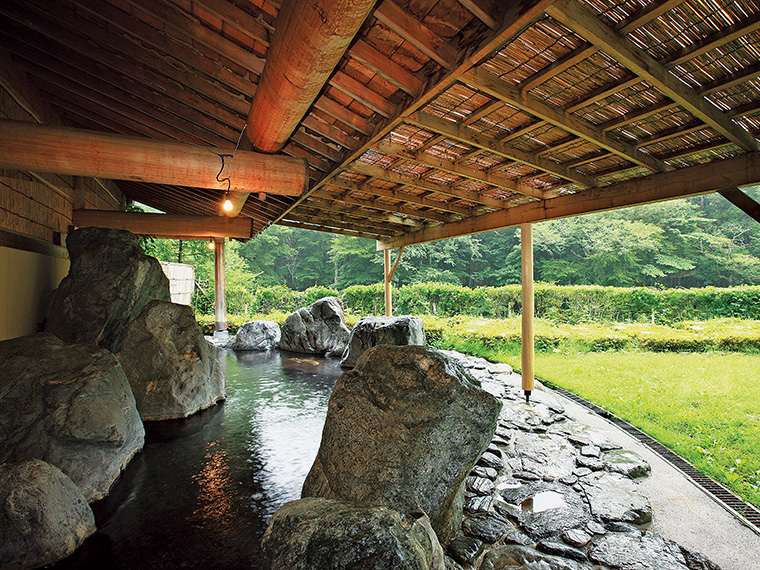 """豊かな自然と大きな岩が織りなすダイナミックな露天風呂。源泉100%の""""美肌の湯""""とともに森林浴気分も楽しめる"""