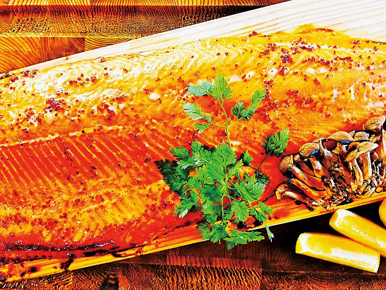 45cmサイズのサーモンを国産の天然山桜の板に乗せたままスモークをかけて焼き上げる極上のサーモンステーキ