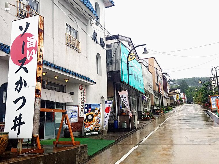 雨の岳温泉街に映える「ソースかつ丼」の看板