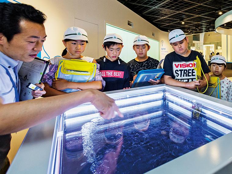 案内スタッフの説明を受けながら「霧箱」の中で繰り広げられる神秘的な様に見入る小学生たち