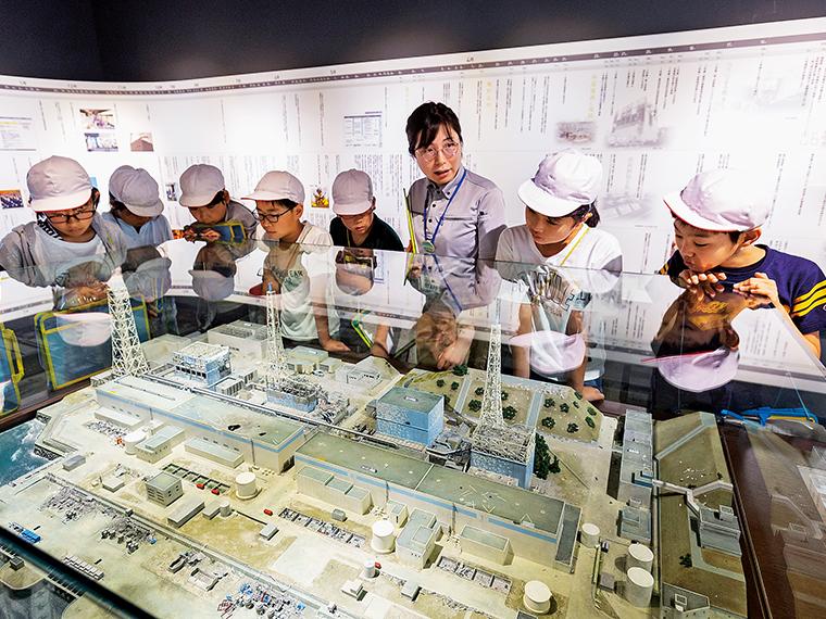 福島第一原発の事故後の模型を見ながら案内スタッフの説明を真剣に聞く小学生たち