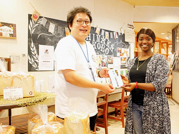 2019年10月3日に、初回の寄付金贈呈が行われた。写真左は「まちなか夢工房」施設長の齋藤さん、寄付金を受け取ったのは「NPO法人 ルワンダの教育を考える会」事務局長のルーシーさん