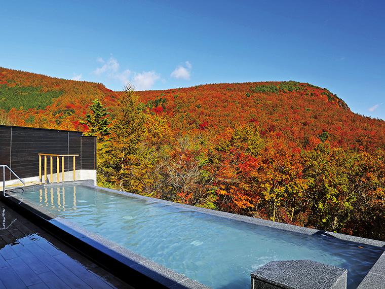 自然との一体感を感じられる露天風呂はやや熱め。紅葉の季節の眺めも見事