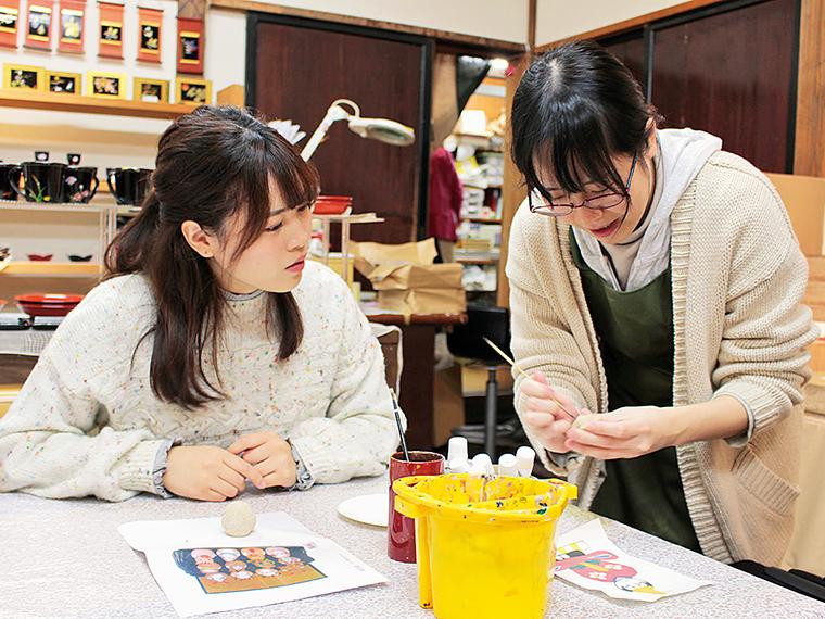 スタッフ・磯さんからレクチャーを受けながら「干支桐のこ人形」手描きにチャレンジ!