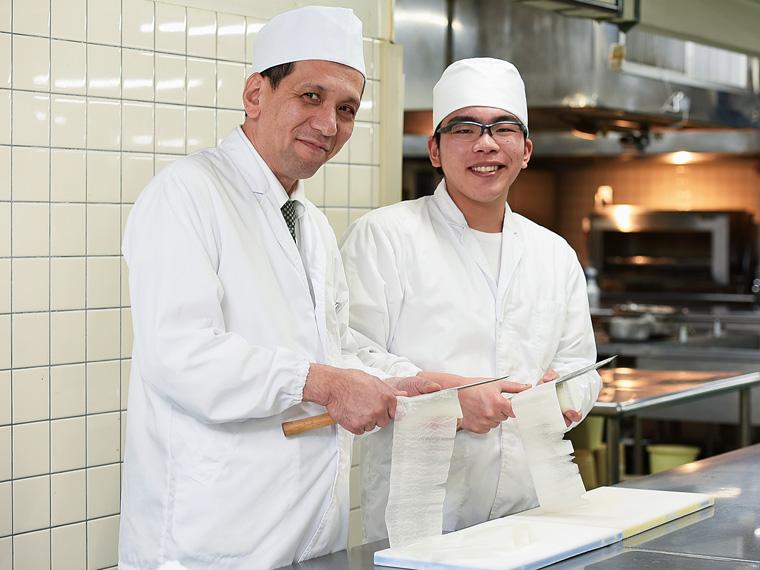 料理長の元宗邦弘さんと入社1年目の田中基貴さん。職場は和気あいあいとした雰囲気