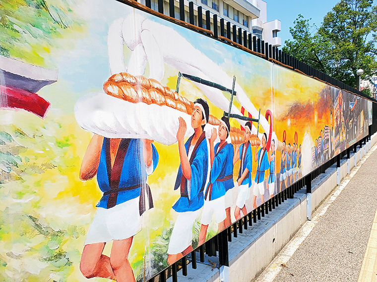 福島市内にある看板に描かれた「わらじまつり」のイラスト。「わらじ音頭」はこんな感じで「大わらじ」を担いで練り歩く夏まつりの時に流されます(2019年から、アレンジが加わった曲にリニューアルしています)
