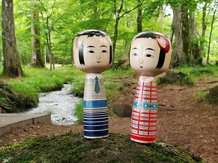 水林公園の一角、裕一が立っている場所あたり。土湯こけしの工人の一人・近藤明裕さんが古関裕而夫妻をイメージして作った「おしどりコケシ」を置いて撮影