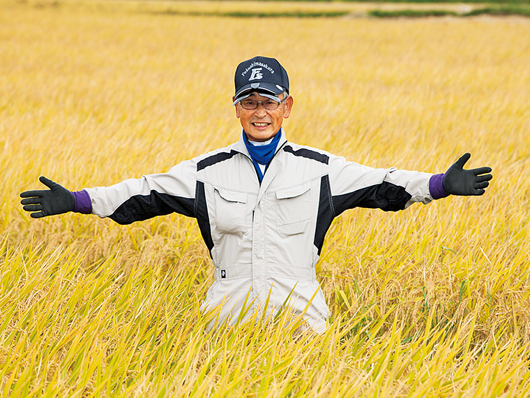 一面黄金色に実った「福、笑い」の田に立つ遠藤さん。田植えから半年間の努力が未来に繋がる