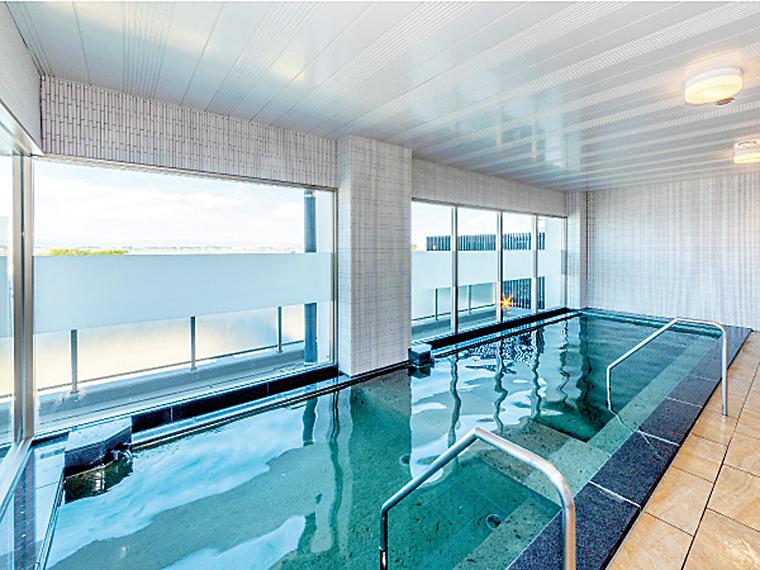 「輪りんの宿」の広々とした大浴場に露天風呂を併設。浴場からは広浦湾や蔵王連峰が見渡せ、心癒される