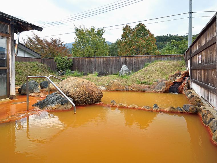 露天風呂では、あふれ出た湯が周りの岩までも赤く染めてしまう
