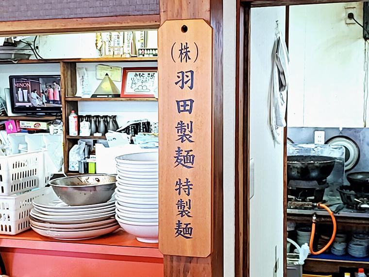 壁に掛けられた「(株)羽田製麺 特製麺」はこだわりの証