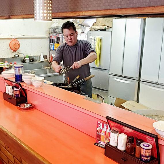 赤いカウンターの内側から繰り出されるのはスタミナ満点の料理とお客さんを元気にする活気