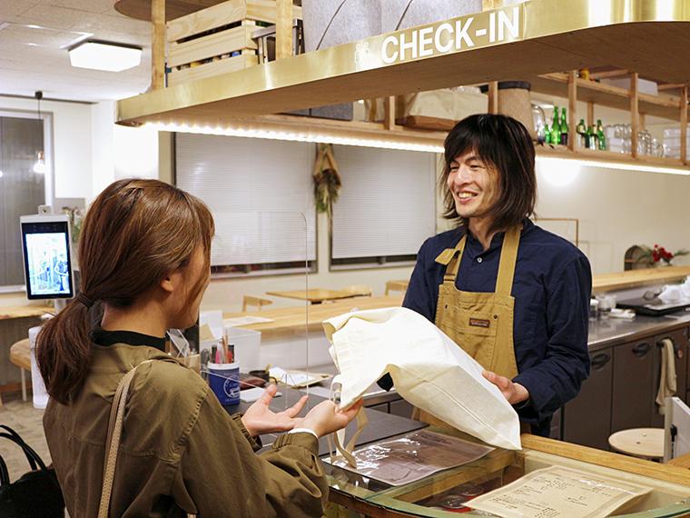 オーナーの伊藤さんが笑顔で出迎えてくれる。宿泊の方にはアメニティー、部屋の管理ができるタブレット端末、ウニコインを渡される